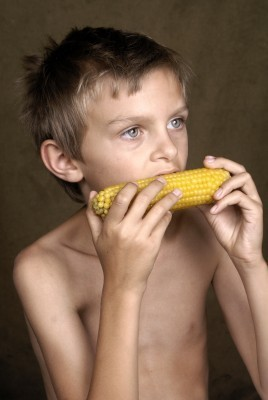 Sick child eating corn